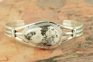 White Buffalo Turquoise set in heavy gauge Sterling Silver. This Beautiful Stone is formed from the minerals Calcite and Iron. It is mined near Tonopah Nevada. Created by Navajo Artist Kathy Yazzie. Signed by the artist.